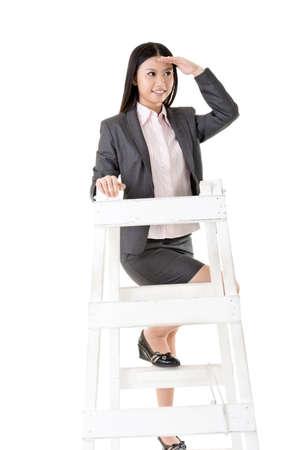 lejos: Mujer de negocios asiática en una escalera que parece lejano, aislado en fondo blanco.