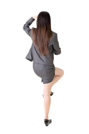 lejos: Mujer de negocios asiática subiendo algo y mirando a lo lejos, de visión trasera retrato aislado en fondo blanco.