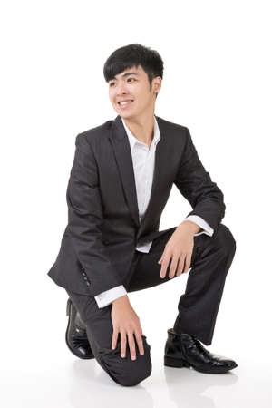 Asian business man squat, full length portrait isolated on white background. photo
