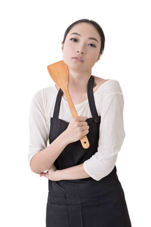 Young Asian housewife hold a spatula in apron, closeup portrait isolated on white background. photo