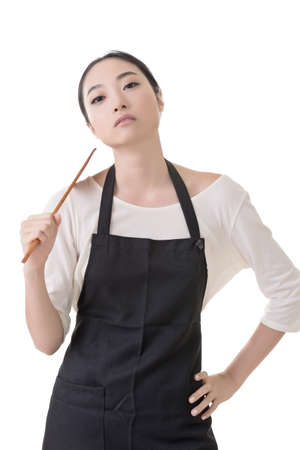 Young Asian housewife hold a spatula in apron, closeup portrait isolated on white background.