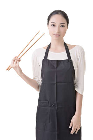Young Asian housewife hold a chopsticks in apron, closeup portrait on white background. photo