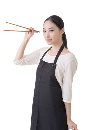 chopstick: Young Asian housewife hold a chopsticks in apron, closeup portrait on white background.