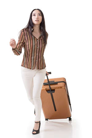 Modern Asian woman running and holding a suitcase, full length portrait isolated on white background. photo