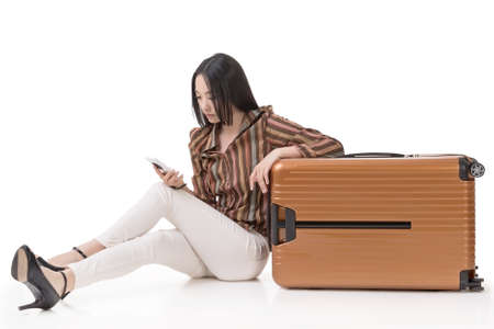 Modern Asian woman sit on ground with a luggage and use a cellphone, full length portrait on white background. photo