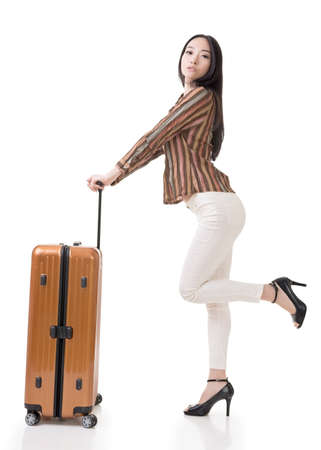 Modern Asian woman stand with a luggage, full length portrait on white background. photo