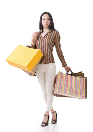 Asian shopping woman holding bags, full length portrait isolated on white. Stock Photo - 25095615