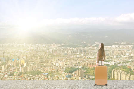 Modern Asian woman stand with a luggage in the roof of high building in the city. photo