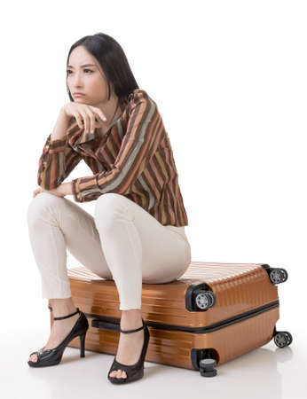Asian woman thinking and sitting on a luggage, full length portrait isolated on white background. photo
