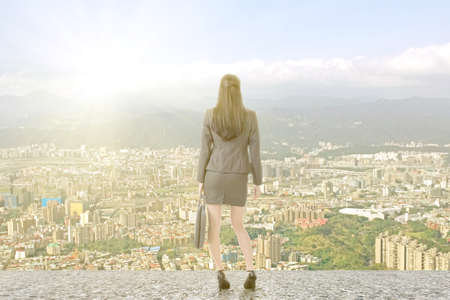 Asian businesswoman standing on the roof and looking at city, with sunrise or sunset. photo