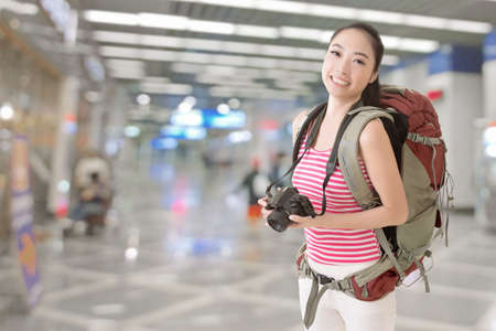travellers: Smiling traveling Asian girl holding a camera and looking at you in the modern airport or train station. Stock Photo