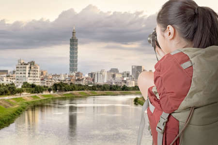 look in mirror: Young backpacker travel and take picture, the tower is the famous landmark, 101 skyscraper, Taipei, Taiwan