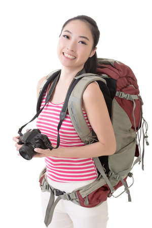 Smiling traveling Asian girl holding a camera and looking at you, closeup portrait.