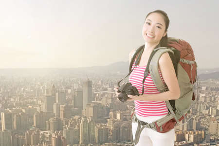 Smiling traveling Asian girl holding a camera and looking at you in the roof of high building. photo