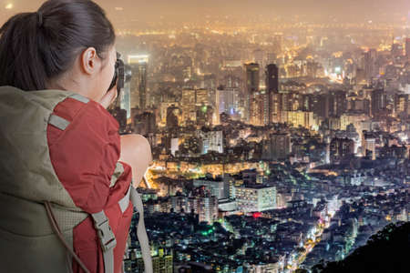 Young backpacker travel and take picture of city night scene in Taipei, Taiwan. photo