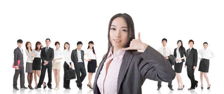 Attractive Asian business woman give you a phone call sign and stand in front of her team. photo