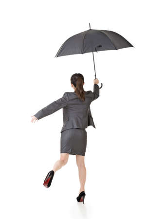 Asian business woman jumping with umbrella. Full length portrait. Rear view. Isolated on the white background. photo
