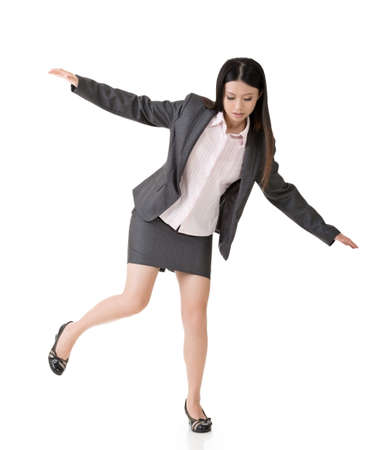 Young asian business woman standing on precipice, trying to balance. Full length portrait. Isolated on the white background. photo
