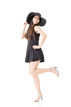 Elegant asian young lady in black dress with hat. Full length portrait. Isolated on the white background. photo