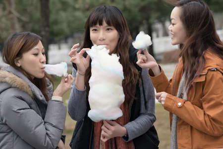 algodon de azucar: Mujer asiática joven feliz comiendo algodón de azúcar con sus amigos en el exterior. Foto de archivo