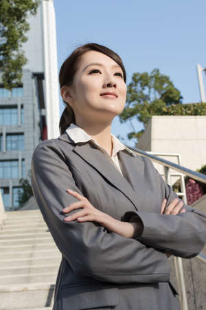 Confident Asian business woman standing in outside of office in sunny day in Taipei, Taiwan photo