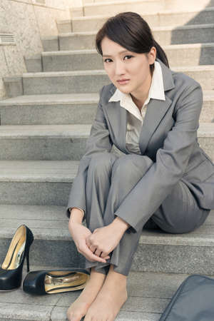 Sad business woman feel helpless and sit on stairs in modern city. photo