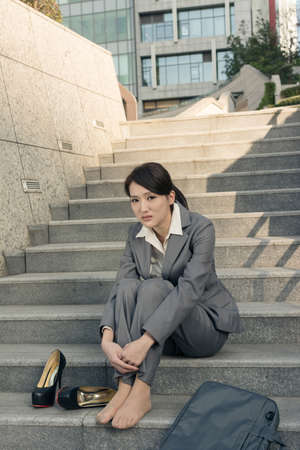 helpless: Sad business woman feel helpless and sit on stairs in modern city.