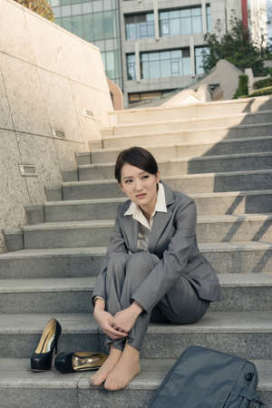 uneasiness: Sad business woman feel helpless and sit on stairs in modern city.