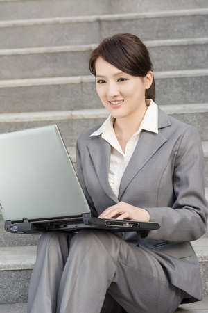 Happy smiling business woman using laptop at outside of office in modern city. photo