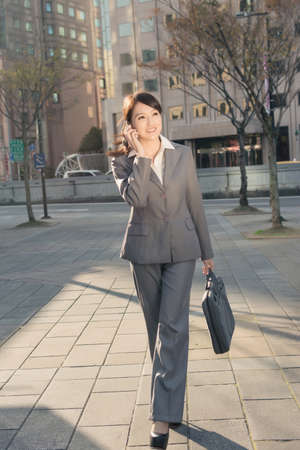 Happy Asian business woman talking on phone and walking on street at sunset in Taipei, Taiwan Stock Photo - 25557389