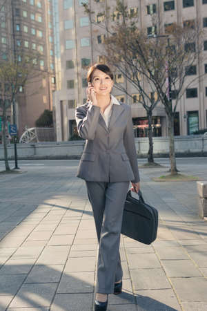 Happy Asian business woman talking on phone and walking on street at sunset in Taipei, Taiwan photo