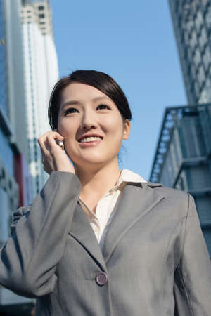 Happy Asian business woman talking on phone and walking on street in modern city of Taipei, Taiwan photo