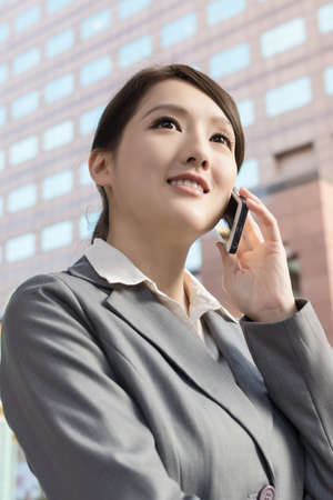 Asian business woman talking on smart phone in modern city. photo