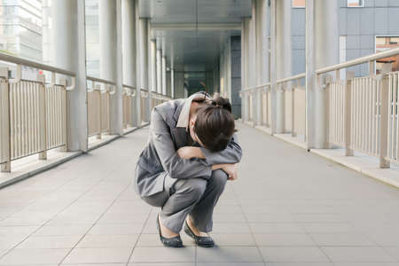 uneasiness: Business woman feel helpless and sadness and squat on ground in city.