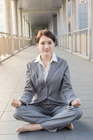 business woman sit on ground and do the lotus position. photo