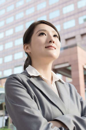 Young pretty Asian business woman portrait,  standing in front of modern buildings. photo