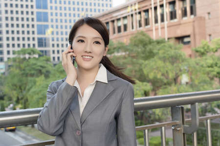 Asian business woman talking on smartphone with copyspace on office buildings in modern city. photo