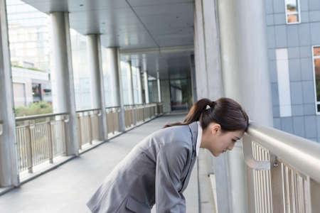 疲れてアジア ビジネスの女性は近代的な都市で手すりに頭を置きます。