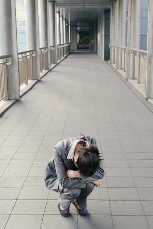 desolation: Business woman feel helpless and sadness and squat on ground in city.