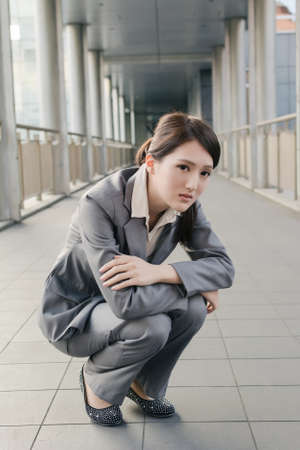 Business woman feel sad and squat on ground look at you in city. photo