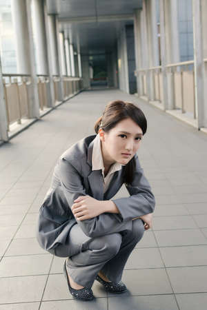 uneasiness: Business woman feel sad and squat on ground look at you in city.