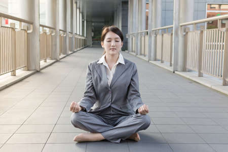 Tranquility or contemplative concept with business woman sit on ground and do the lotus position. photo