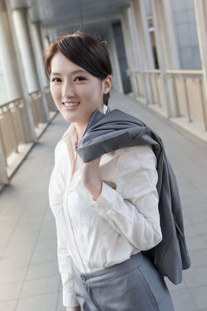 Happy smiling business woman of Asian put coat on shoulder go off work. photo