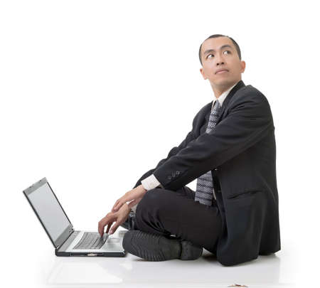 sitting on the ground: Asian businessman using laptop on ground looking back, full length portrait on white.