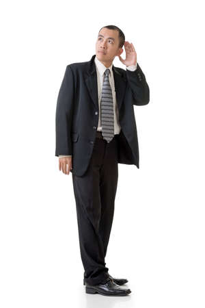 heed: Mature Asian business man hear, full length portrait isolated on white. Stock Photo