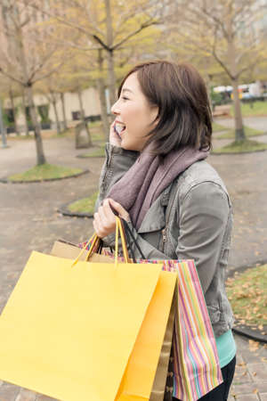 Asian woman talk on phone hold shopping bags at street after raining in Taipei, Taiwan,  Asia. photo