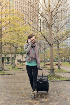 Attractive Asian woman holding suitcase and talking on phone at street, Taipei, Taiwan. photo