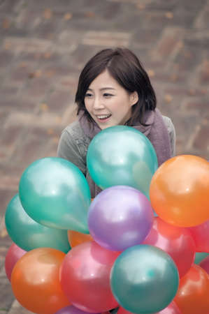 Young woman playing and holding balloons at park in Taipei, Taiwan, Asia. photo