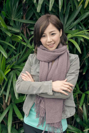 Elegant Asian woman standing in front of green leaves wall in outdoor. photo