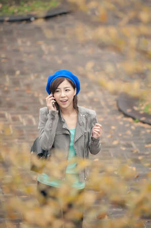 Cheerful Asian lady talking on cellphone at street in the park, Taipei, Taiwan. photo